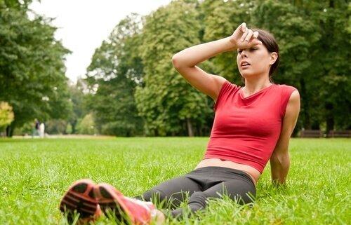 Femme en tenue de sport assise sur l'herbe