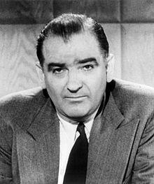 Photo en noir et blanc du buste d'un homme regardant droit vers la caméra.