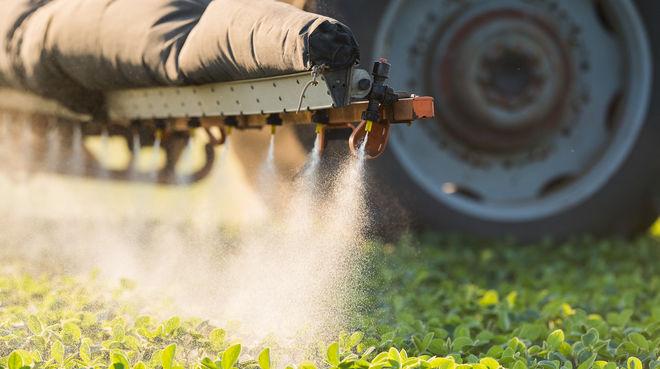 Un tracteur est en train d'épandre des pesticides sur un champ dans l'Union européenne