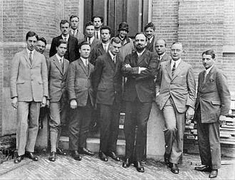 Photo en noir et blanc. Devant un immeuble, plusieurs hommes debout font face à l'appareil-photo.