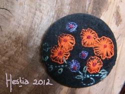bouton noir aux fleurs oranges