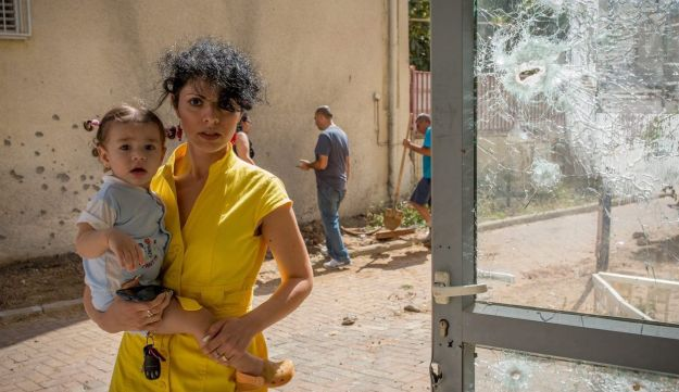 A woman and her baby standing near an area hit by a missile launched from Gaza in the town of Sderot, Israel. July 15, 2014