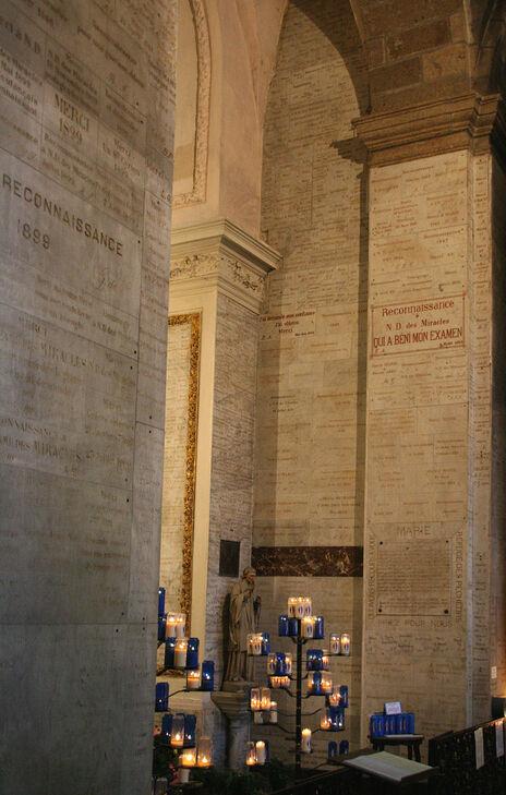 Murs et pilier de l'église recouverts du sol au plafond d'ex-voto en marbre gravé.