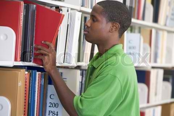 1237844-752853-male-student-selecting-book-from-library-shelf