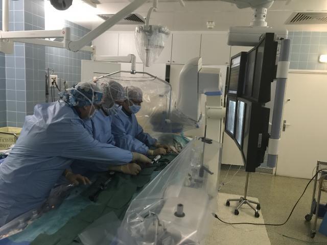 Les médecins travaillent face à un mur d'écrans qui leur permet de visualiser en quasi-temps réel le trajet de la valve et son positionnement.