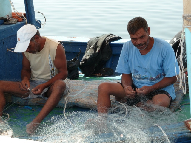 Pendant la pause, les pêcheurs remaillent les filets endommagés