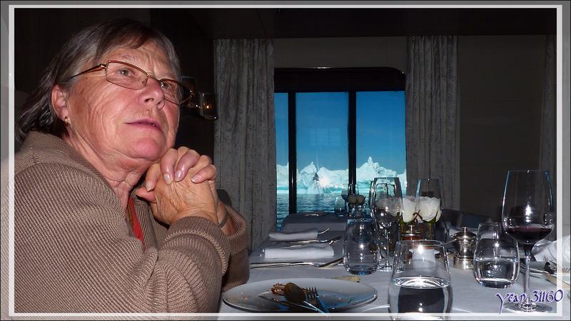 A table : l'air pensif de Madame pendant que l'iceberg défile loin devant les sabords du restaurant - L'Austral à Ilulissat - Groenland