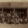 Crow men incuding Pretty Eagle (sitting 7th from right), Spotted Horse (sitting 6th from right), and