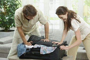 5754741-couple-packing-for-holiday-trying-to-close-suitcase-full-with-clothes