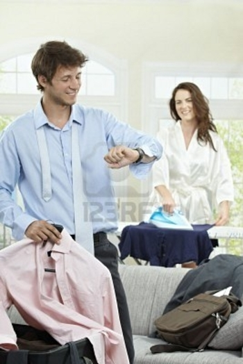 5754674-young-businessman-going-to-business-trip-looking-at-his-watch-woman-ironing-in-the-backgroun