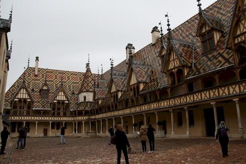 """C'est en 1443 que Nicolas Rolin, chancelier du duché de Bourgogne, rédigea la charte de fondation de l'Hôtel-Dieu de Beaune : après huit années de travaux, le premier malade fut accueilli le 1er janvier 1452. C'est un véritable chef d'oeuvre d'architecture, mondialement connu et célèbre pour l'éclat de sa cour d'honneur, la splendeur de ses toits aux tuiles multicolores et vernissées, ses salles de malades, et particulièrement la fameuse """" Salle des Pôvres """", son apothicairerie, et tous ses trésors parmi lesquels figure le remarquable polyptyque du Jugement Dernier de Roger Van Der Weyden.  Depuis 1982, l'ensemble de bâtiments distribués autour de la cour d'honneur n'accueille plus aucun malade et l'Hôtel-Dieu, devenu monument historique, reçoit plus de 400 000 visiteurs par an : fidèle à la tradition hospitalière, il est ouvert tous les jours sans exception."""