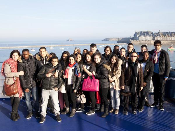 Photo de groupe des élèves, à l'arrière-plan, la mer et les remparts de Saint-Malo sous le soleil