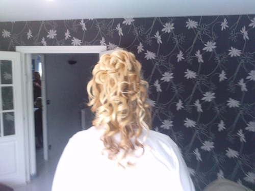 coiffure de mariée en hauteur avec moitié de cheveux relachée bouclée.