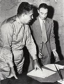 Photo en noir et blanc. Deux hommes debout, un habillé d'un uniforme, l'autre d'un complet, discutent près d'une table.