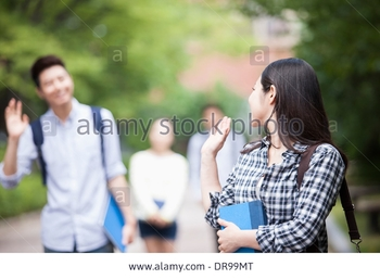 a-university-student-greeting-a-friend-in-the-campus-holding-books-DR99MT