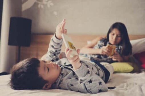Deux enfants allongés sur un lit avec un téléphone portable.