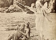 À la gauche de la photo, un chevalier qui semble blessé est supporté par une femme, les deux étant assis par terre. À la droite, une fée en position debout brandit une baguette.