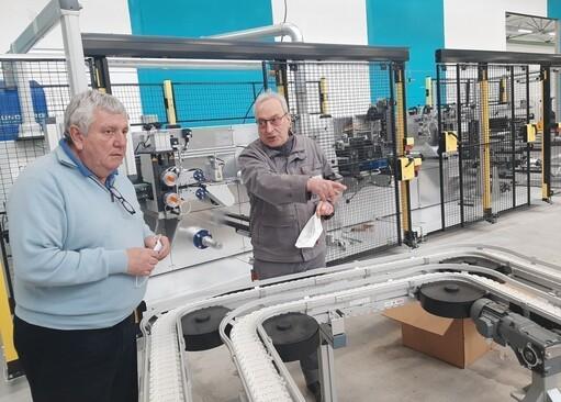 Devant l'une des machines de production, Guy Hascoët (à gauche), le président de la Coop des masques et Gérard Boissières, automaticien de l'entreprise Cera Engineering, fabricant de la machine installée dans l'usine de Grâces, près de Guingamp (Côtes-d'Armor).