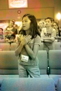 Preteen fille debout avec ses mains sur son coeur.  Elle chante.