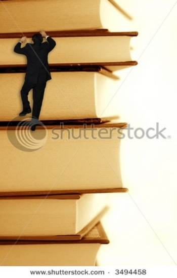 stock-photo-pile-of-books-with-a-businessman-climbing-it-3494458