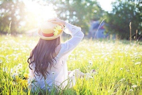 Femme assise au soleil dans un champs avec un chapeau de paille.