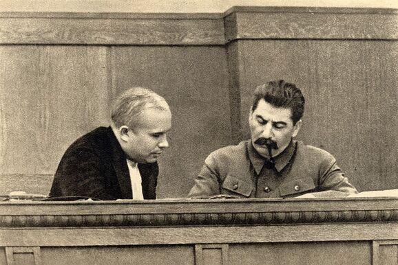 Photographie de deux hommes étudiant des documents sur un bureau.