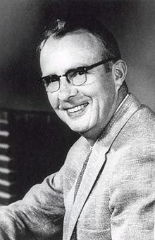 Photo en noir et blanc. Photo du torse d'un homme souriant qui porte un veston et des lunettes.