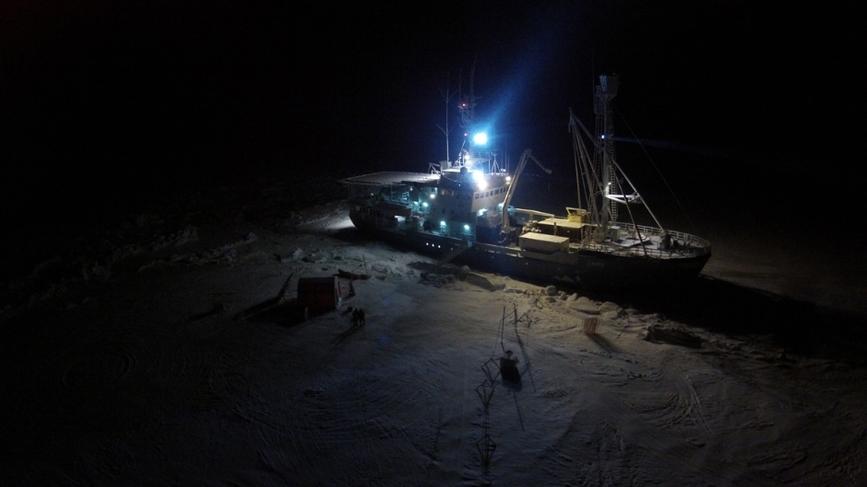 Fugleperspektiv-bilde av skipet Lance, innfryst i isen i Arktis. Det er mørkt.