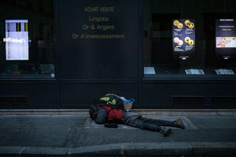 Un SDF dort sur une bouche d'aération de métro pour se tenir chaud devant une boutique d'achat et de vente d'or, à Paris le 29 janvier 2017