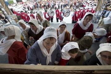 Les bénévoles personnifiant les Filles du roi signent une toile souvenir lors de leur passage à Québec
