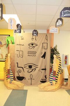 Al ver esta imagen me ha inspirado que con esta decoración se puede hacer un trono para el delegado del día en un aula de educación infantil, convirtiéndole en faraón por un día. Para ello utilizaríamos una de sus sillas y la adornaríamos con motivos egipcios. Pudiendo colocar también la decoración que aparece en la imagen y en medio la silla decorada simulando el trono en un palacio egipcio.: