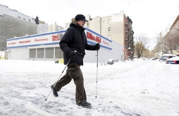 a-pedestrian-using-ski-poles-walks-past-a-closed-pharmacy-on-first-avenue-at-930am-after-a-major-sno
