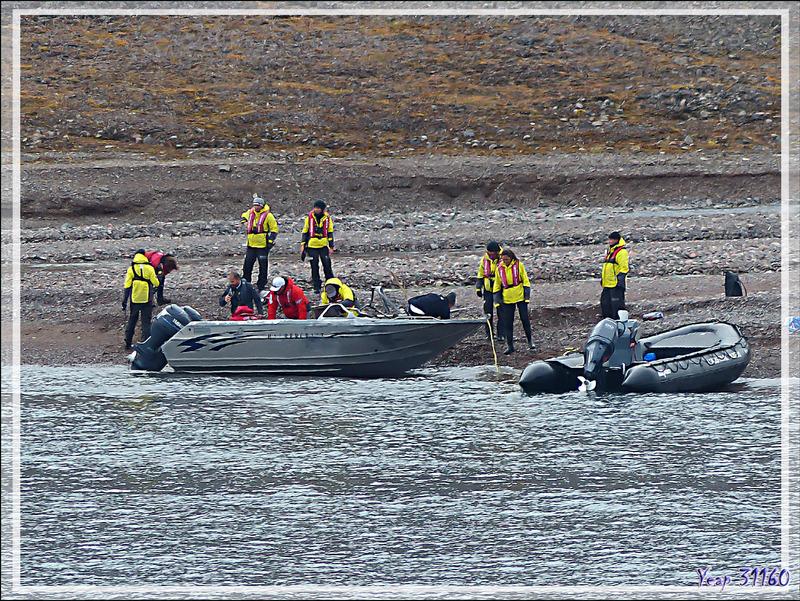 Au loin, en bordure de l'eau, une épave, c'est un bateau retourné en aluminum de type Harbercraft, équipé de deux moteurs - Guillemard Bay - Prince of Wales Island - Nunavut - Canada