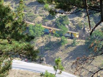 Au zoom, le train jaune (lourdement tagué) au dessus de la route 116, vers Fontpédrouse