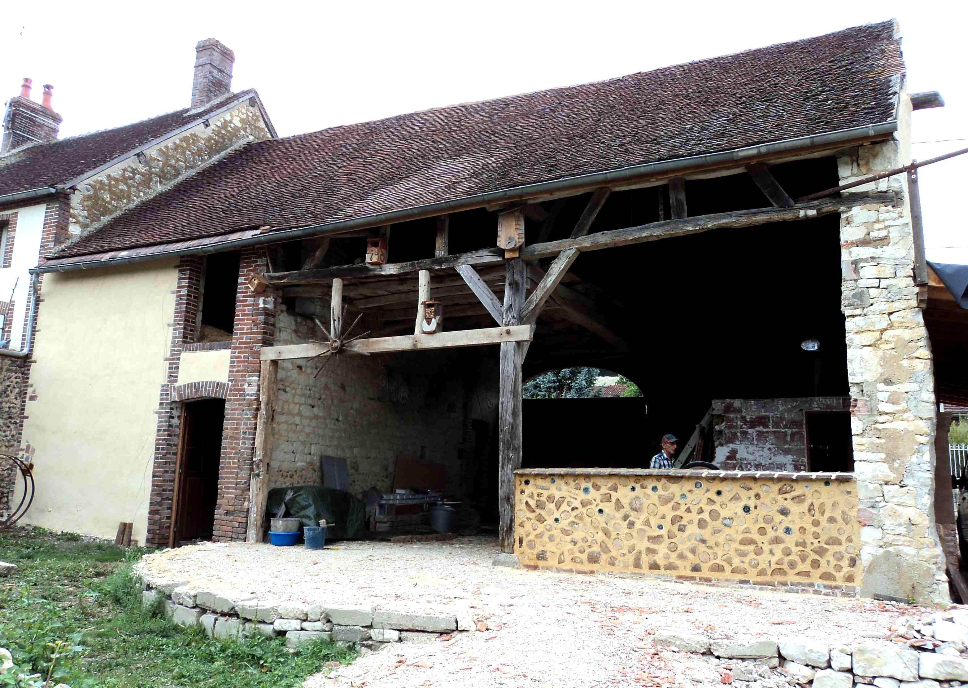 Façade de la grange et nouveau mur de bois cordé