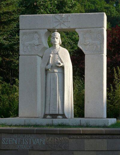 Statue blanche d'un roi portant une cape, un sceptre et une couronne.