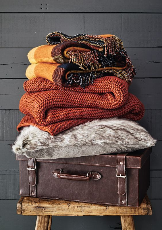 Channel ski-lodge chic with chunky-knit cushions and throws. Burnt orange shades matched with mustard, navy and yellow creates an earthy, warm feel.