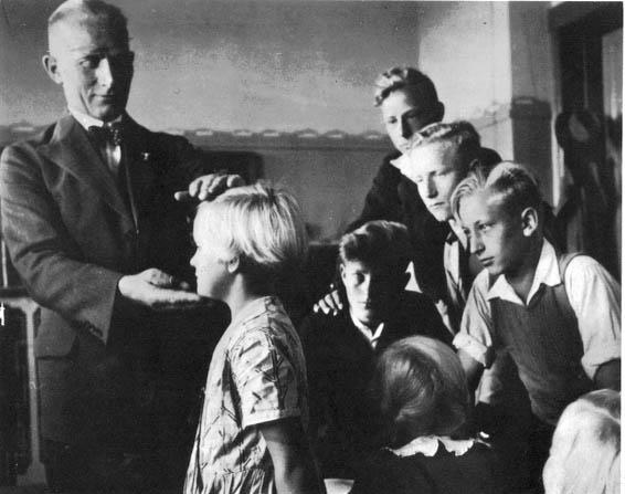 Photo : un instituteur tient dans ses mains la tête d'une petite fille blonde, sous les yeux de ses camarades