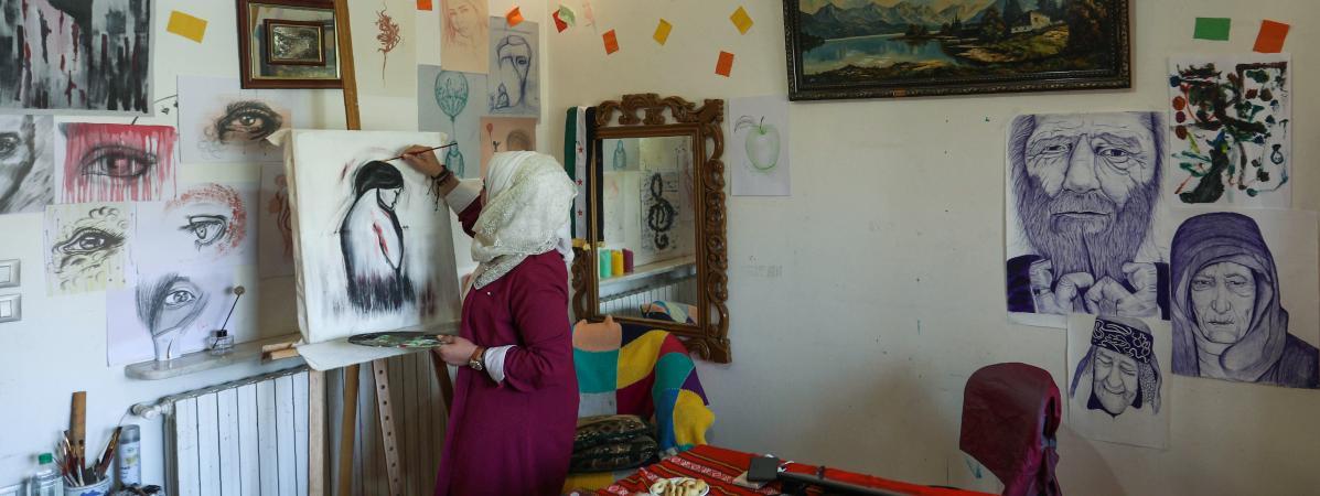 L\'artiste syrienne Amani al-Ali travaille sur une peinture dans son appartement d\'Idlib.