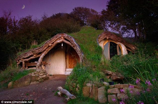 La lune se lève sur la maison qui est couverte avec de l'herbe et se niche dans ses environs boisés