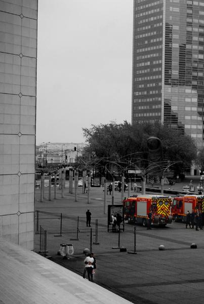 deux personnes enlacées au pieds de l'arche de la Défense avec des pompiers en arrière-plan