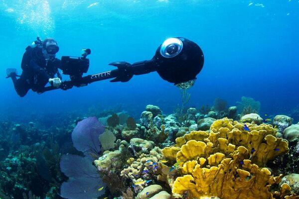 Christophe Bailhache en pleine prise de vue sur le récif corallien de l'île Glover, dans les Cayes du Belize, un archipel de la mer des Caraïbes. Son drôle d'appareil photographique permet de réaliser un outil de promenade virtuelle à la manière d'un Street View. Le programme XL Catlin Seaview Survey (initialement Catlin Seaview Survey), lancé en 2012, étudie les récifs coralliens de la planète. Celui-ci, au Belize, est l'un des plus grands du monde, après celui de la Grande Barrière de corail, en Australie. © Richard Vevers, Catlin Seaview Survey