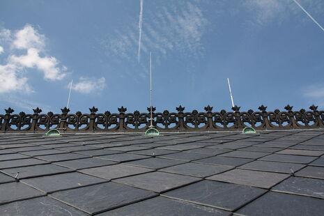 Photographie en contre-plongée des ardoises carrées du toit