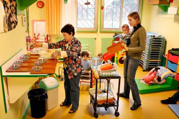 Auxiliaires de puériculture dans une crèche préparant le goûter des enfants dans des plateaux individuels