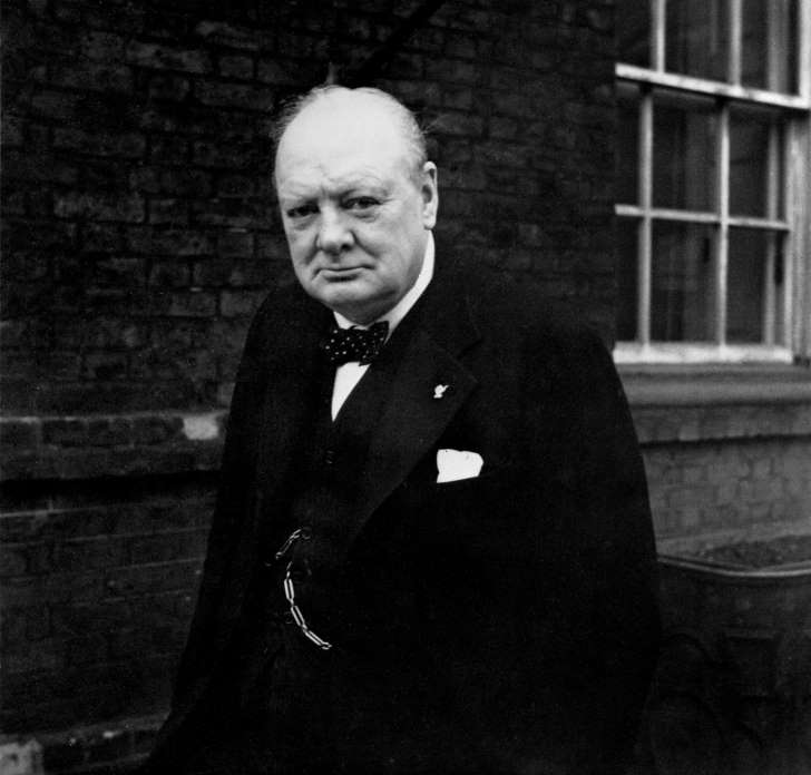 Winston Churchill During The Second World War In The United Kingdom, The Prime Minister Winston Churchill poses outside 10 Downing Street, London, England, wearing a 'Thumbs up' badge on 21 November 1941. (Photo by Capt. Horton/ IWM via Getty Images)