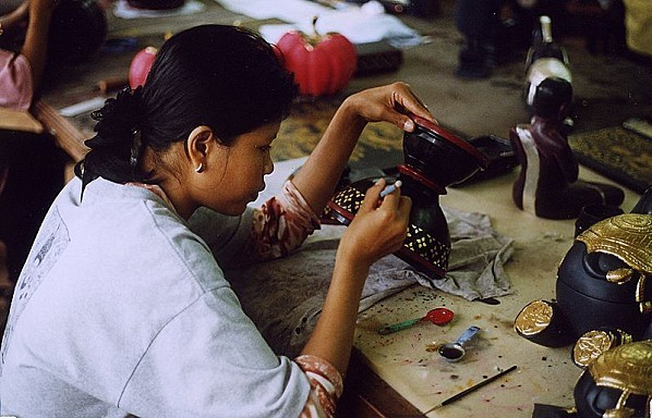 Here, a woman is working with a lacquered