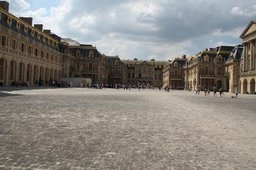C'est le père du Roi Soleil, Louis XIII qui fut à l'origine de l'installation de la royauté à Versailles. Zone forestière et marécageuse, le jeune roi y chassait avec son père Henri IV. Plus tard, pris d'agoraphobie et souhaitant s'éloigner de sa mère Marie de Médicis qui assurait la régence après l'assassinat du roi par Ravaillac, Louis XIII préférait passer son temps à Versailles. Un premier château est alors construit en 1623 sur le domaine de Versailles pour accueillir le roi lorsqu'il voulait pratiquer la chasse. Il sera agrandi en 1631 pour à ce moment être orné de jardins à la française et d'aménagements pour la promenade royale. Malheureusement lorsque commença le règne de Louis XIV, Anne d'Autriche conseillée par le Cardinal Jules Mazarin quitta Versailles qui resta inhabité jusqu'aux travaux ordonnés par le jeune roi en 1660. Cette bâtisse est conservée par le Roi Soleil comme base pour son propre château. C'est aujourd'hui la partie qui entoure la cour d'Honneur.