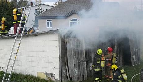 Une formation pour les pompiers avec feu réel sur un bâtiment