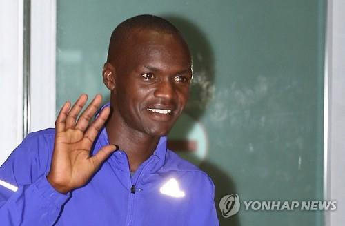 Wilson Loyanae Erupe, un marathonien né au Kenya qui espère devenir un citoyen sud-coréen, les vagues à caméras après son arrivée à l'aéroport international d'Incheon, le 23 Juin, 2015. (Yonhap)