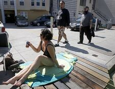 Brooke Cooley enjoys a cold beverage while sunbathing on Cesar Chavez Boulevard near Mission Street in San Francisco on Saturday. Residents upset with a proposed ban on sitting or lying on sidewalks staged events across the city to protest the legislation. Photo: Paul Chinn, The Chronicle
